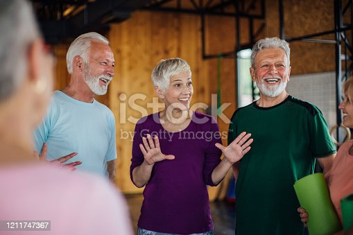 1047537292 istock photo Senior woman joking with her friends from yoga class 1211747367