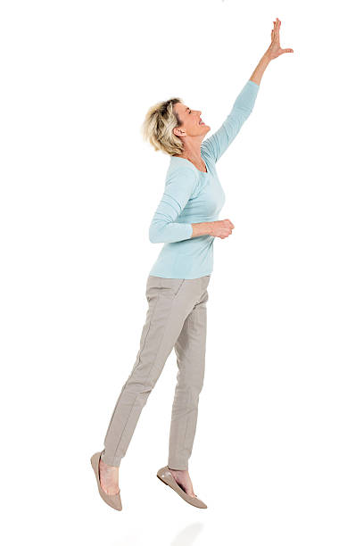 senior woman jumping up and reaching out stock photo