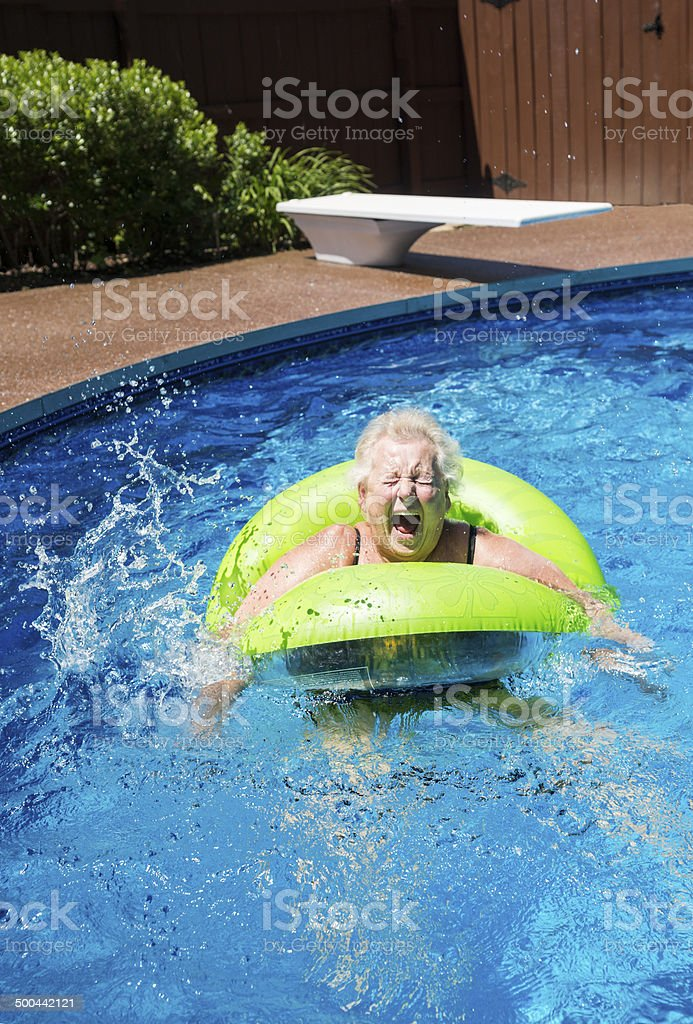 Senior woman jumps into the pool royalty-free stock photo