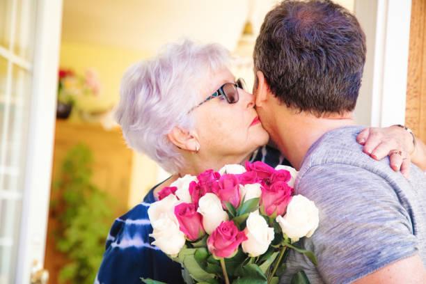 ältere frau küsst reife sohn bringen strauß rosen - alles gute zum geburtstag sohn stock-fotos und bilder