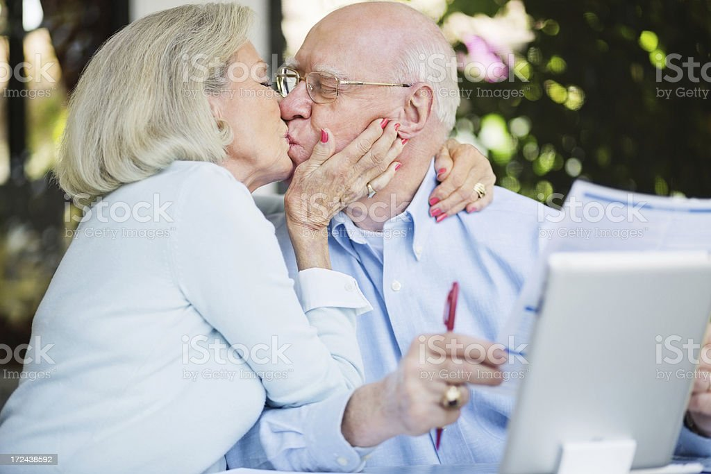 Senior Woman Kissing Husband While Calculating Home Finance royalty-free stock photo