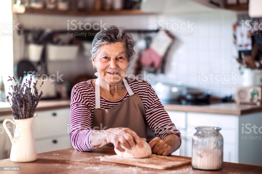 A senior woman kneading dough in the kitchen at home. royalty-free stock photo