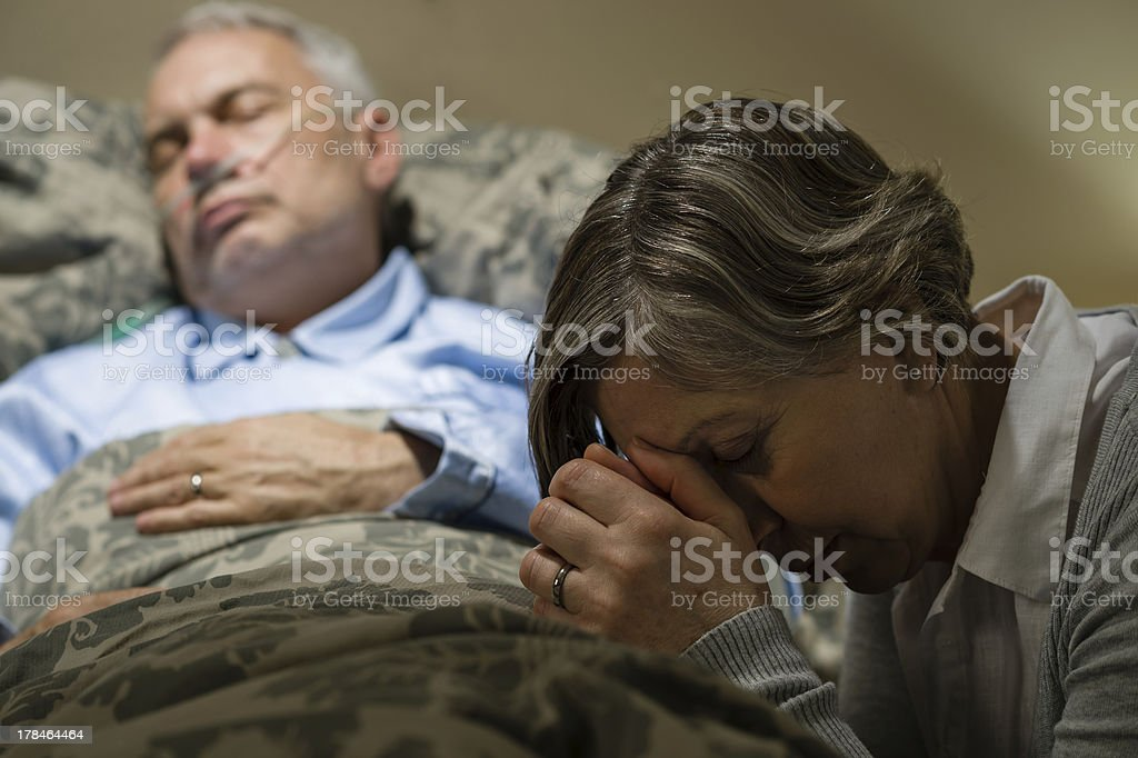 Senior woman kneeling prays over a sick man in bed stock photo