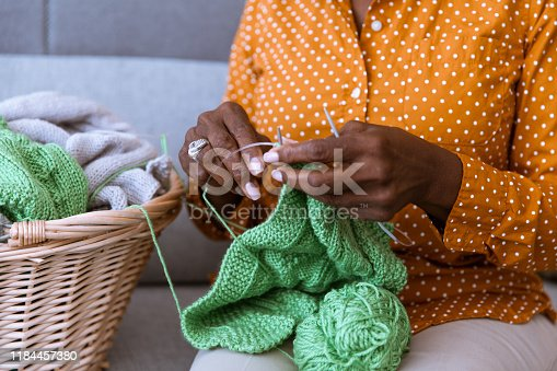 African American senior sitting on the couch and knitting at home