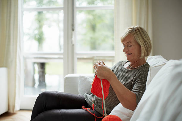 senior woman knitting on sofa - lavorare a maglia foto e immagini stock