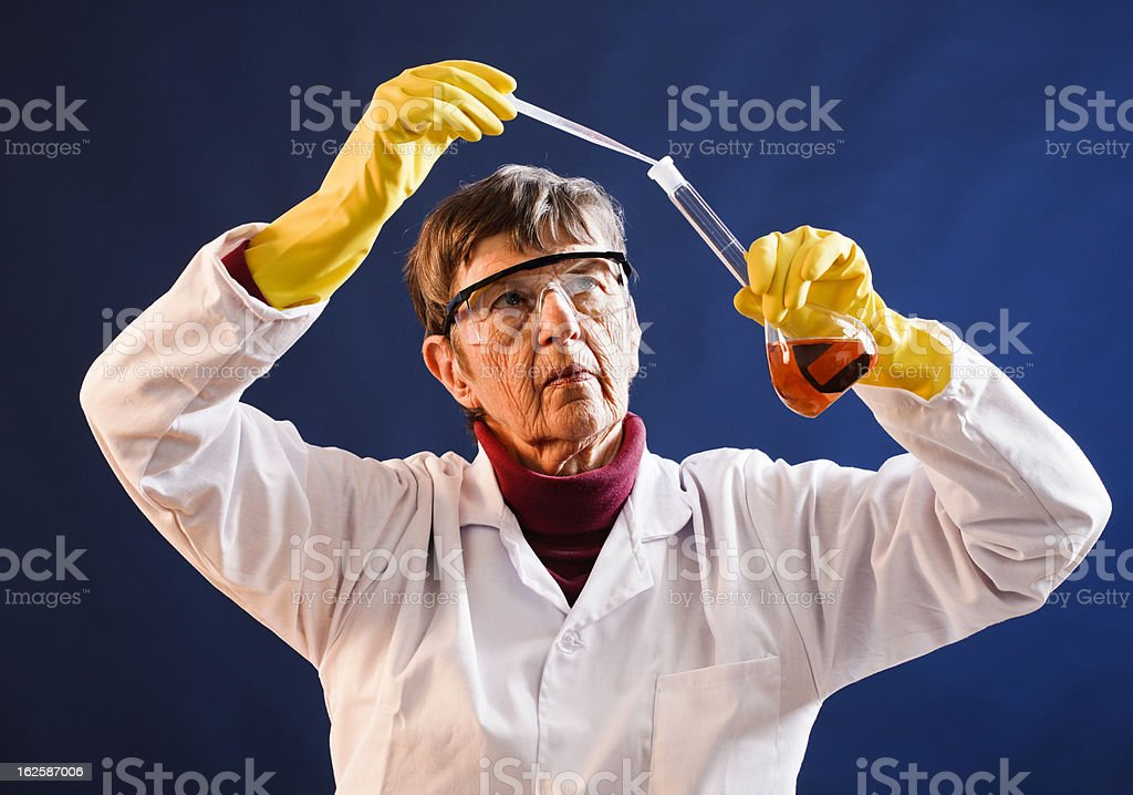 Senior woman lab technician concentrates on adding liquid to flask stock photo