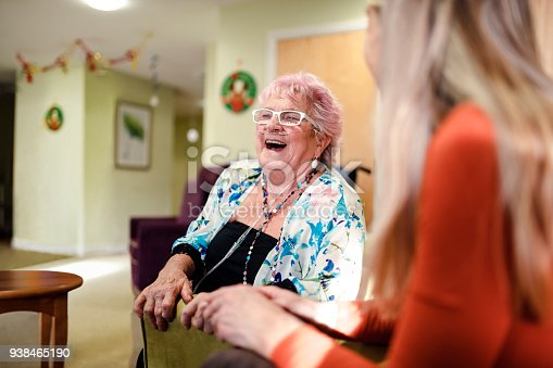 Senior woman talking to a younger woman who is visiting her while she is living in the care home. The senior woman has pink hair