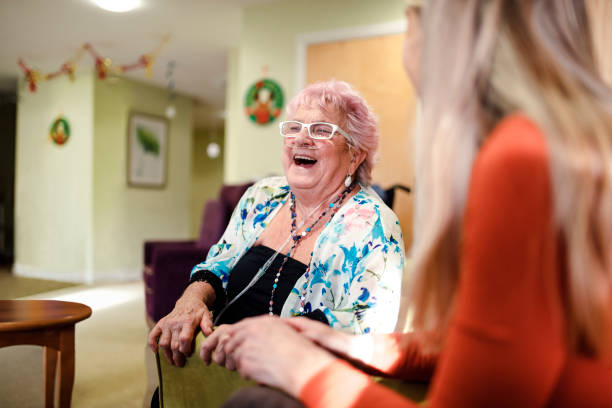 Senior Woman Laughing Senior woman talking to a younger woman who is visiting her while she is living in the care home. The senior woman has pink hair medical oxygen equipment stock pictures, royalty-free photos & images
