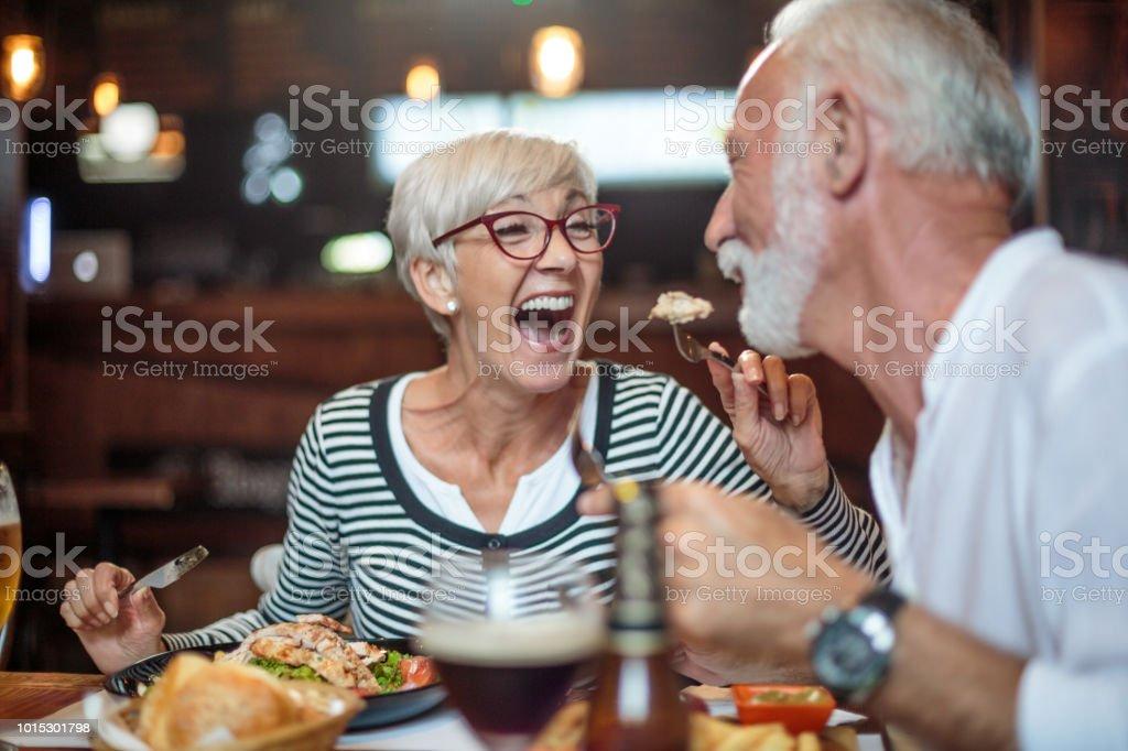 Senior vrouw lachen terwijl voeden haar mannelijke partner in het restaurant - Royalty-free Actieve ouderen Stockfoto