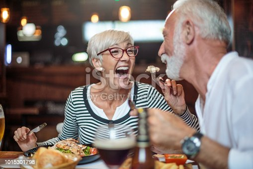 Active senior couple having a lunch in the restaurant and woman is feeding her partner. Drinks and food are on the table.