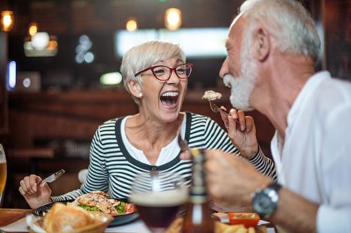 Senior Vrouw Lachen Terwijl Voeden Haar Mannelijke Partner In Het Restaurant Stockfoto en meer beelden van Actieve ouderen
