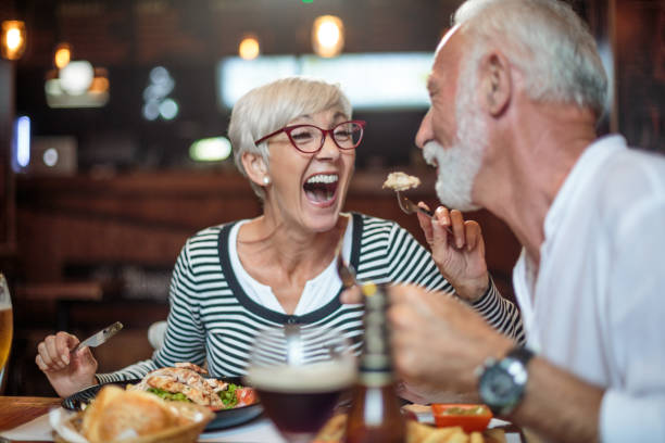 senior woman laughing while feeding her male partner in the restaurant - nutrire foto e immagini stock