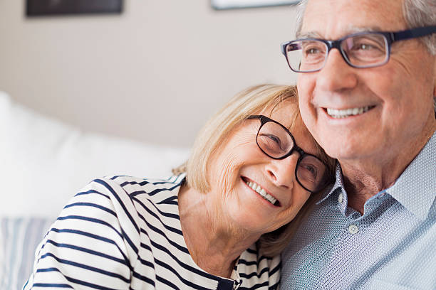 Senior woman leaning head on senior man's shoulder A photo of senior woman leaning head on senior man's shoulder. Happy loving couple are looking away. They are wearing eyeglasses at home. 60 64 years stock pictures, royalty-free photos & images