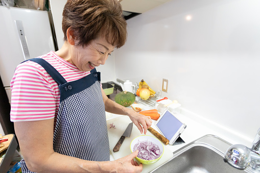 Senior woman learning cooking using tablet