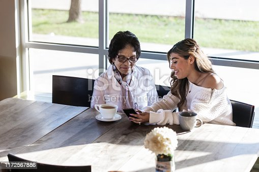 Hispanic senior woman attentively listens as her young adult granddaughter teaches her to use a smartphone. They are having coffee in a trendy coffee shop.