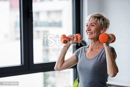 Active good looking elderly woman smiling and holding dumbbells while working out indoors