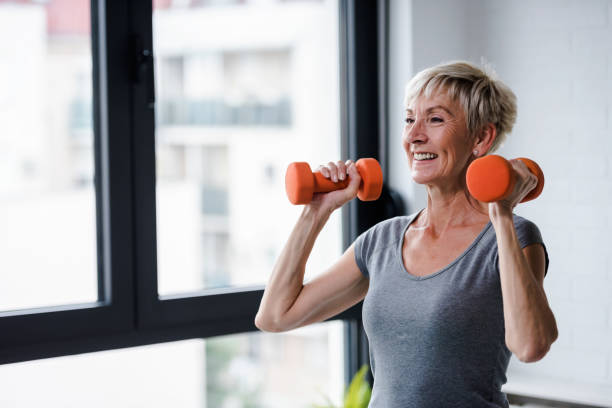 üst düzey kadın halter kaldırma - sağlıklı yaşlılar stok fotoğraflar ve resimler