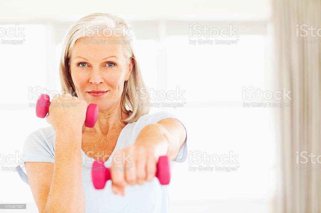 Senior Woman Lifting Dumbbells stock photo