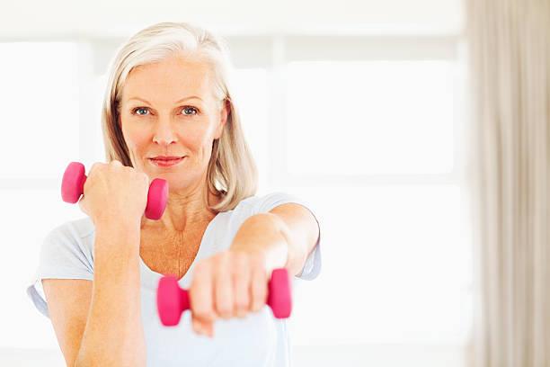 senior frau heben kurzhanteln - rosa training stock-fotos und bilder