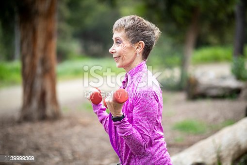851958232 istock photo Senior Woman Lifting Weights in Forest 1139999369