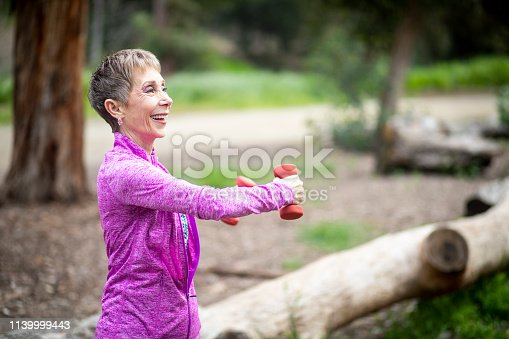 851958232 istock photo Senior Woman Lifting Weights in Forest 1139999443
