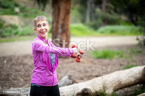 851958232 istock photo Senior Woman Lifting Weights in Forest 1139999493