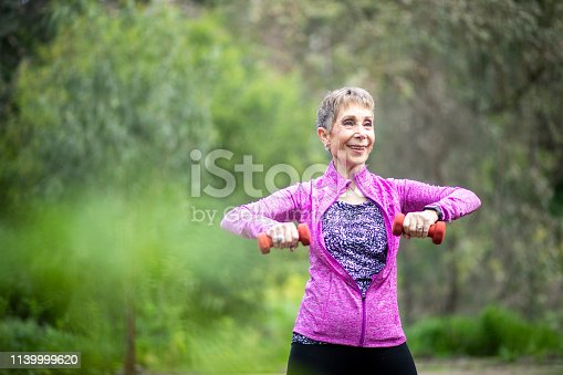 851958232 istock photo Senior Woman Lifting Weights in Forest 1139999620