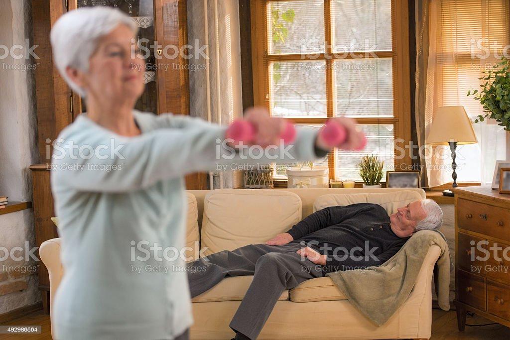 Senior Woman Lifting Weights In Living Room Husband Sleeping