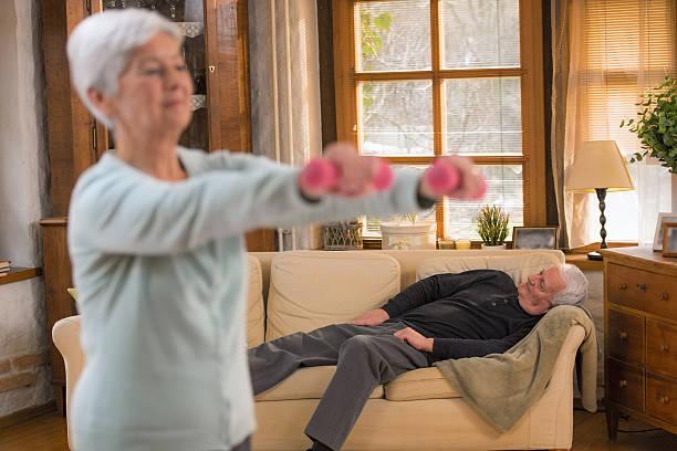 donna anziana sollevamento pesi nel soggiorno, marito notte - divano procrastinazione foto e immagini stock
