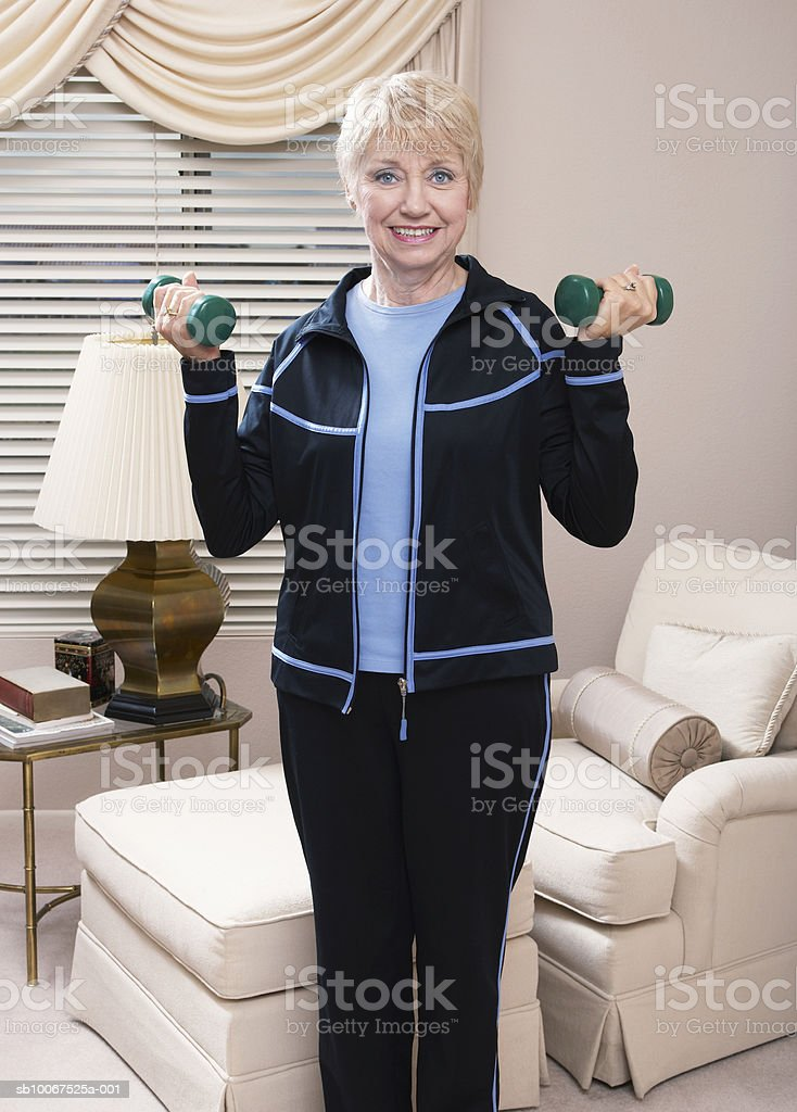 Senior woman lifting weights, smiling royalty-free stock photo