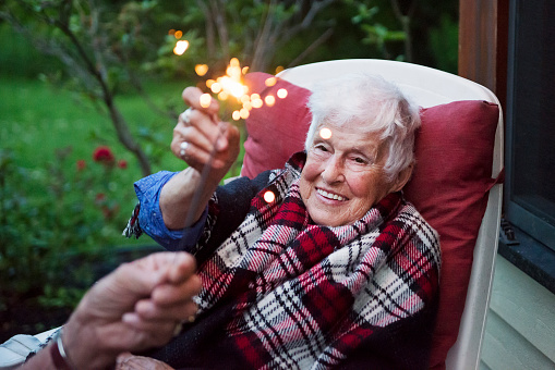 Senior woman, in her eighties, lighting some sparklers outdoors on a warm summer night. She is wearing casual clothes and a plaid scarf for a small family gathering. Horizontal outdoors waist up shot with copy space.
