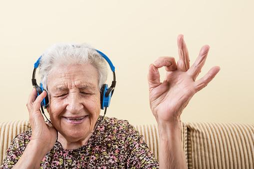 senior woman making okay sign while wearing headphones to listening music