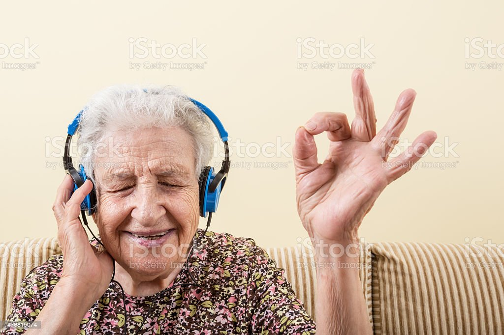 senior woman listening music stock photo