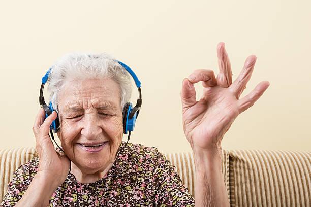 senior mujer escuchando música - geriatría fotografías e imágenes de stock