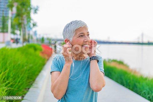 497687118 istock photo Senior woman listening music with headphones. 1254529206