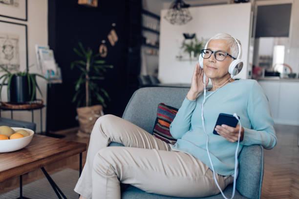hogere vrouw die aan een podcast bij haar woonkamer luistert - podcast stockfoto's en -beelden
