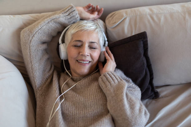 Senior woman listening to music stock photo
