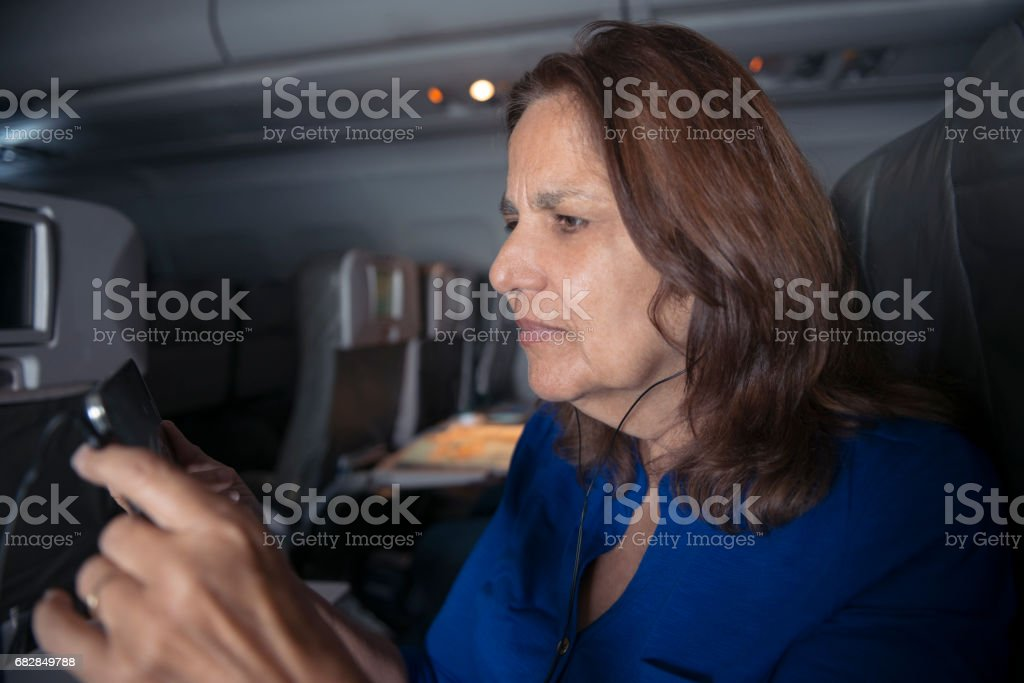 Ältere Frau hört Podcast auf Flugzeug Lizenzfreies stock-foto