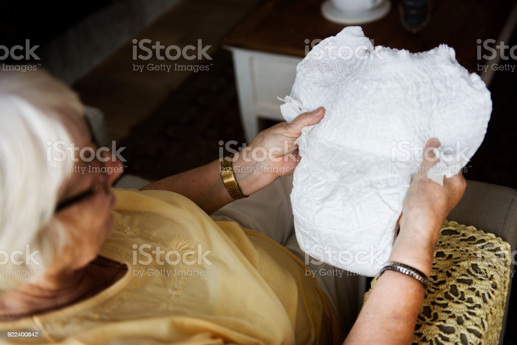 Senior woman looking at a diaper stock photo