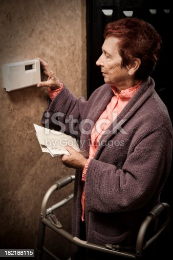 A stock photo of a beautiful senior woman standing with her walker who is looking at the thermostat and holding bills worried over ability to pay.