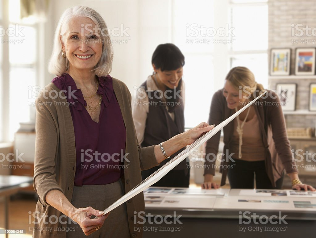 Senior woman looking at designs with colleagues stock photo
