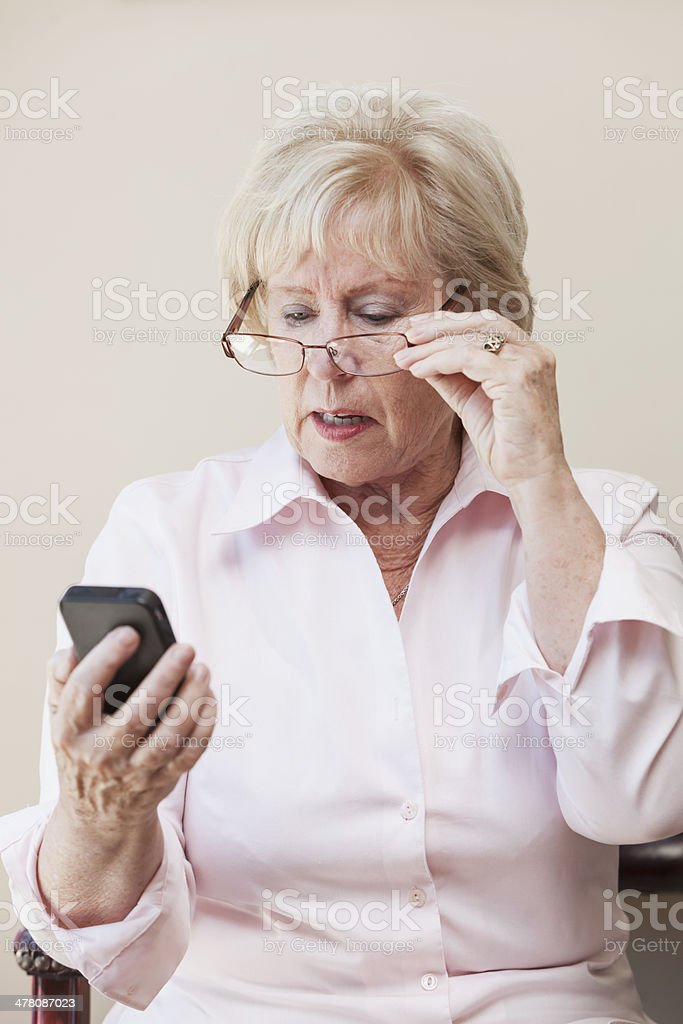 Senior woman looking at mobile phone royalty-free stock photo