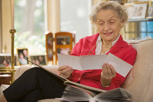 Senior woman looking at photographs stock photo