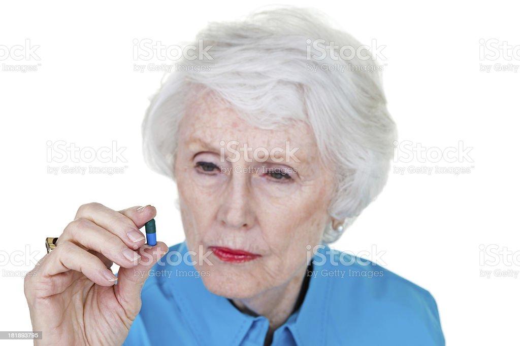 Senior woman looking at pill royalty-free stock photo
