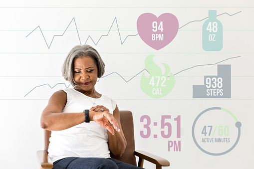 An active African American senior woman checks activity level and health status on her smart watch. Heart rate, water consumption, steps taken, activity level and the current time are overlaid in a digitally generated image.