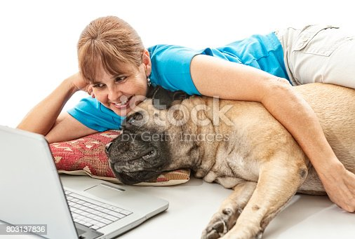 Senior woman looking at the computer with her pet bull mastiff while enjoying a cup of coffee