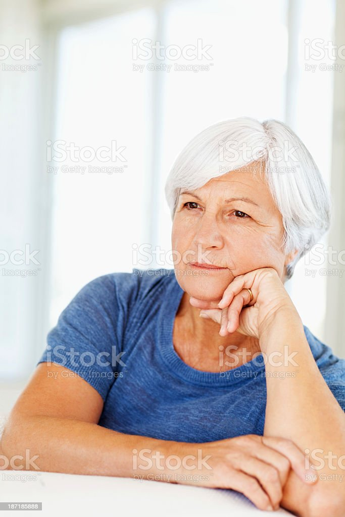 Senior Woman Looking Away With Hand On Chin At Home royalty-free stock photo