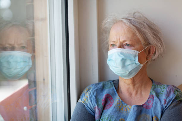 senior woman looking out of the during quarantine cause of COVID-19 stock photo