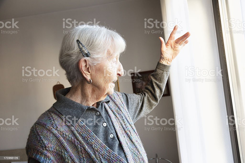 senior woman looking out of the window royalty-free stock photo