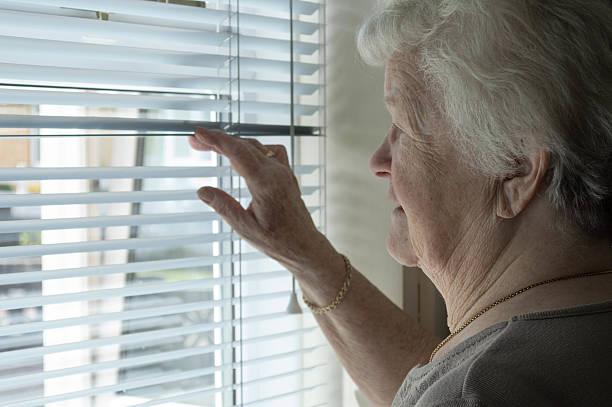 senior femme regardant par la fenêtre à volets - indiscret photos et images de collection